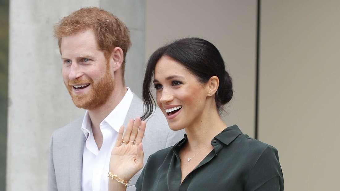 Prinz Harry und Herzogin Meghan, die winkt, blicken zur Seite.