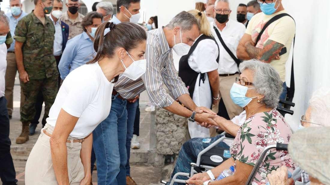 König Felipe und Königin Letizia sprechen mit alten Menschen, Felipe hält die Hand einer Person.