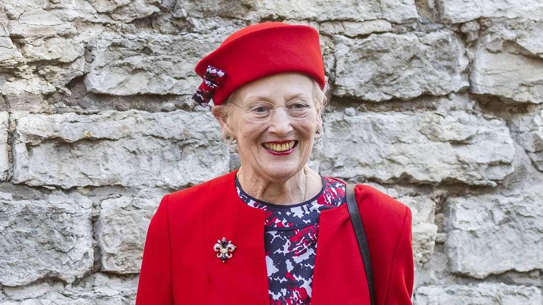 Königin Margrethe II. von Dänemark trägt ein rotes Kostüm und einen passenden Hut.