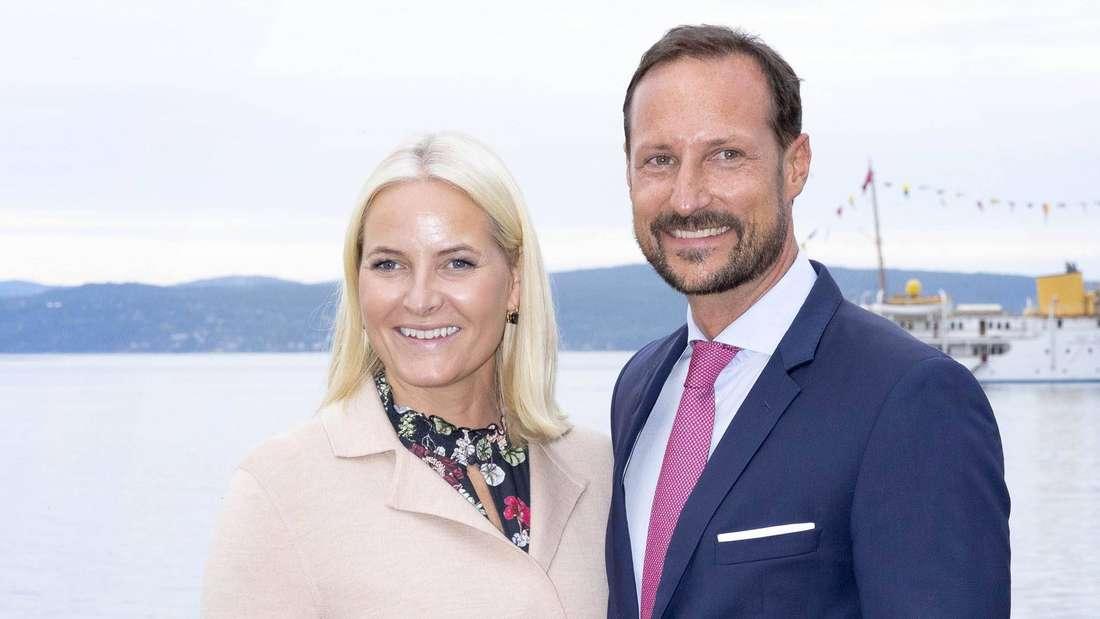 Kronprinzessin Mette-Marit und Kronprinz Haakon von Norwegen stehen nebeneinander und lächeln (Symbolbild).