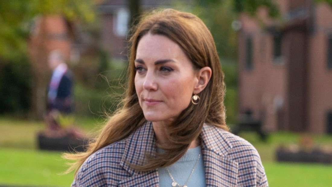 Herzogin Kate blickt zur Seite, ihr Haar weht im Wind.