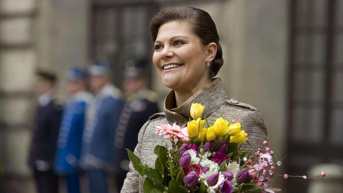 Kronprinzessin Victoria von Schweden hält einen Blumenstrauß in der Hand und lächelt (Symbolbild).