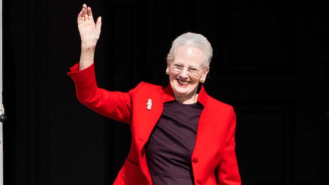 Königin Margrethe II. von Dänemark trägt eine rote Jacke, lächelt und winkt mit der rechten Hand.