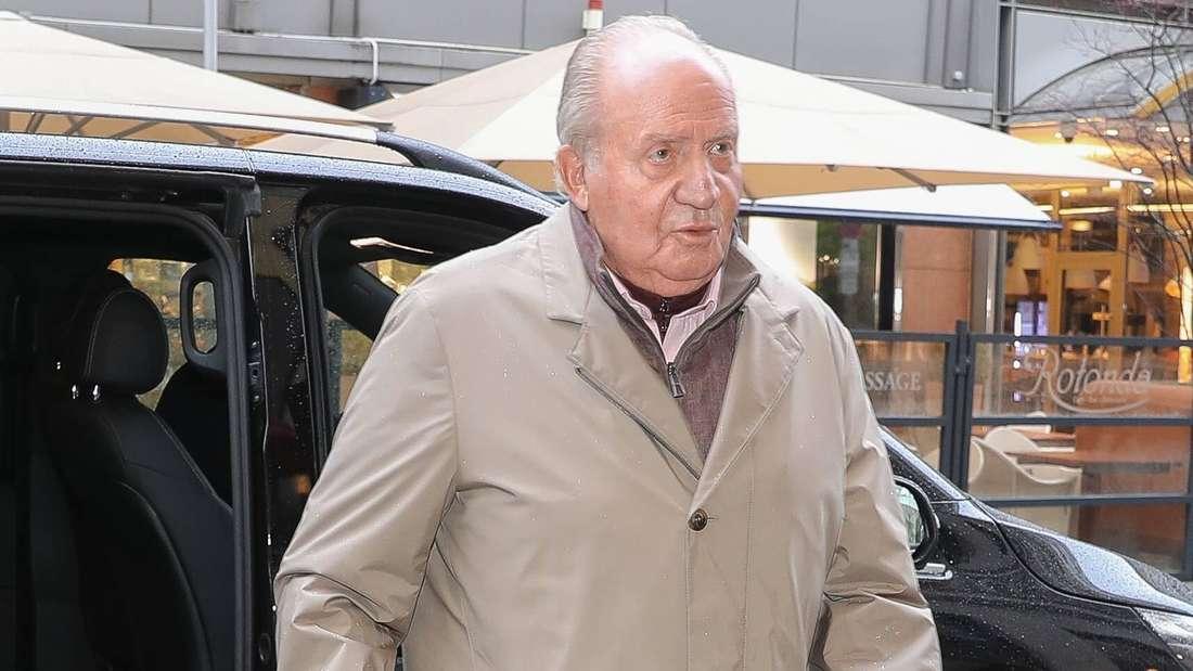 Juan Carlos I. trägt einen beigen Mantel und einen braunen Pullover und schaut geradeaus (Symbolbild).