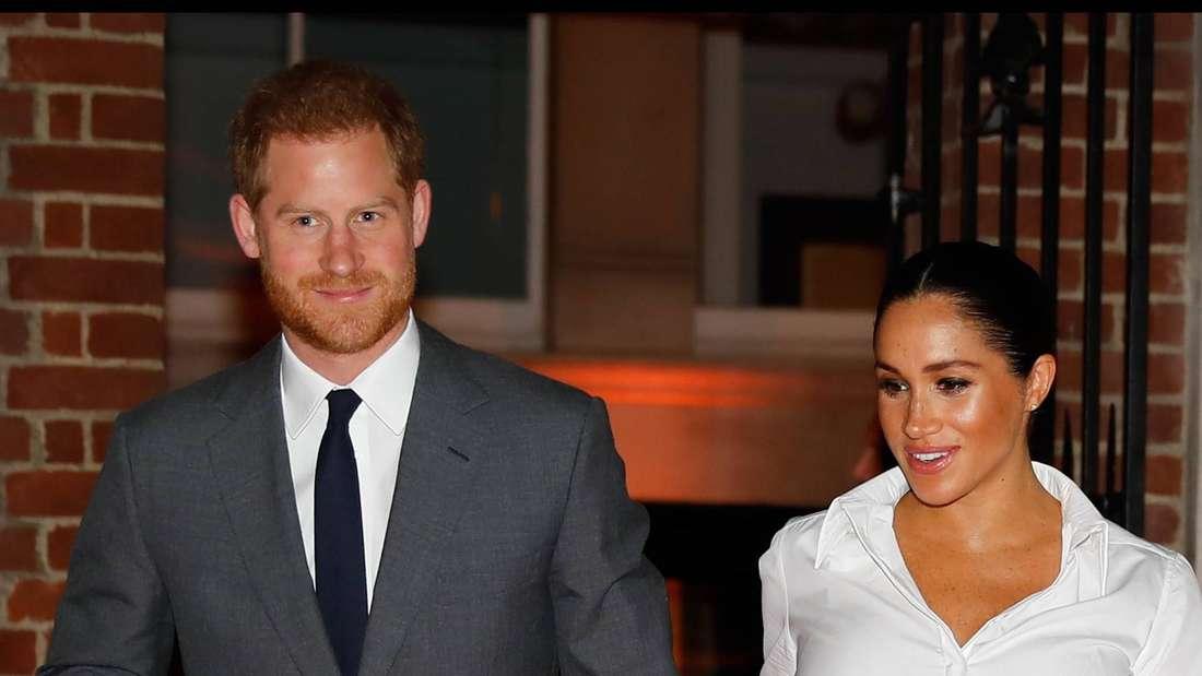 Prinz Harry und Herzogin Meghan gehen Hand in Hand nebeneinander her.