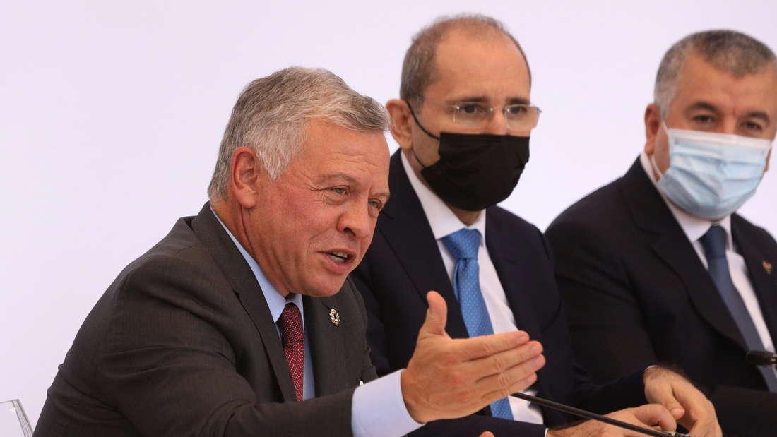 Der jordanische König Abdullah spricht bei einer Konferenz. Zwei Männer mit Maske sitzen mit am Tisch.