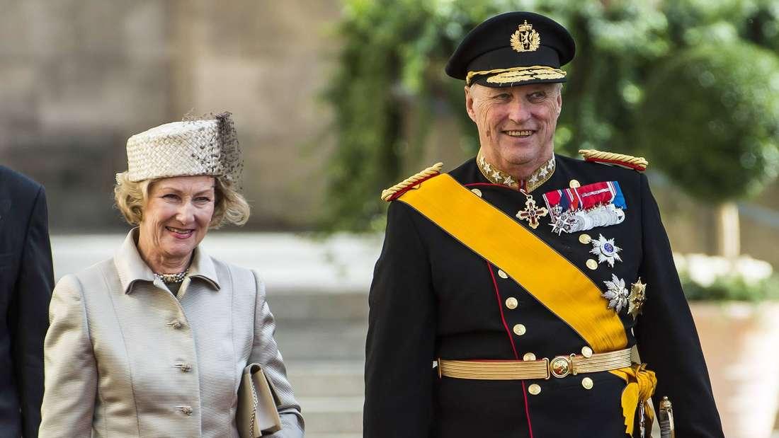 Königin Sonja und König Harald gehen lächelnd nebeneinander her, er trägt eine Uniform.