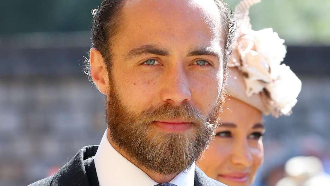 James Middelton steht im Anzug draussen in der Sonne. Hinter ihm ist Schwester Pippa zu sehen.