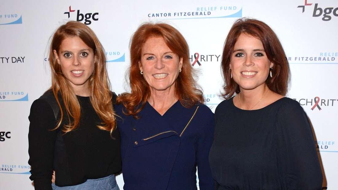 Prinzessin Beatrice, Sarah Ferguson und Prinzessin Eugenie stehen Arm in Arm nebeneinander und lächeln.