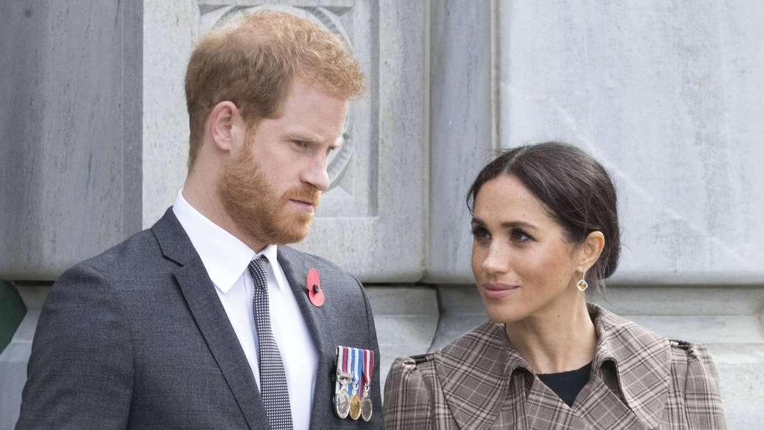 Herzogin Meghan blickt zu ihrem Ehemann Prinz Harry, der ernst nach unten schaut.