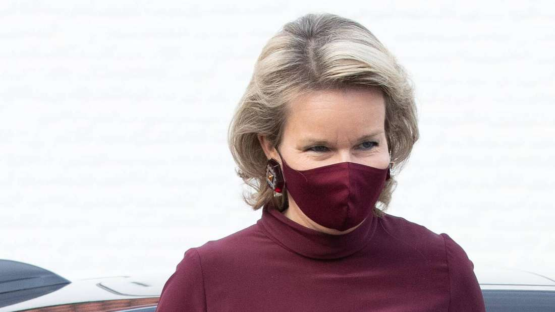 Königin Mathilde von Belgien trägt eine dunkelrote Schutzmaske und blickt zur Seite.
