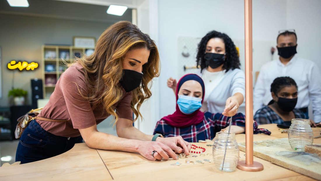 Rania von Jordanien beugt sich über eine Schmuckauslage und betrachtet mit Maske die Auswahl.