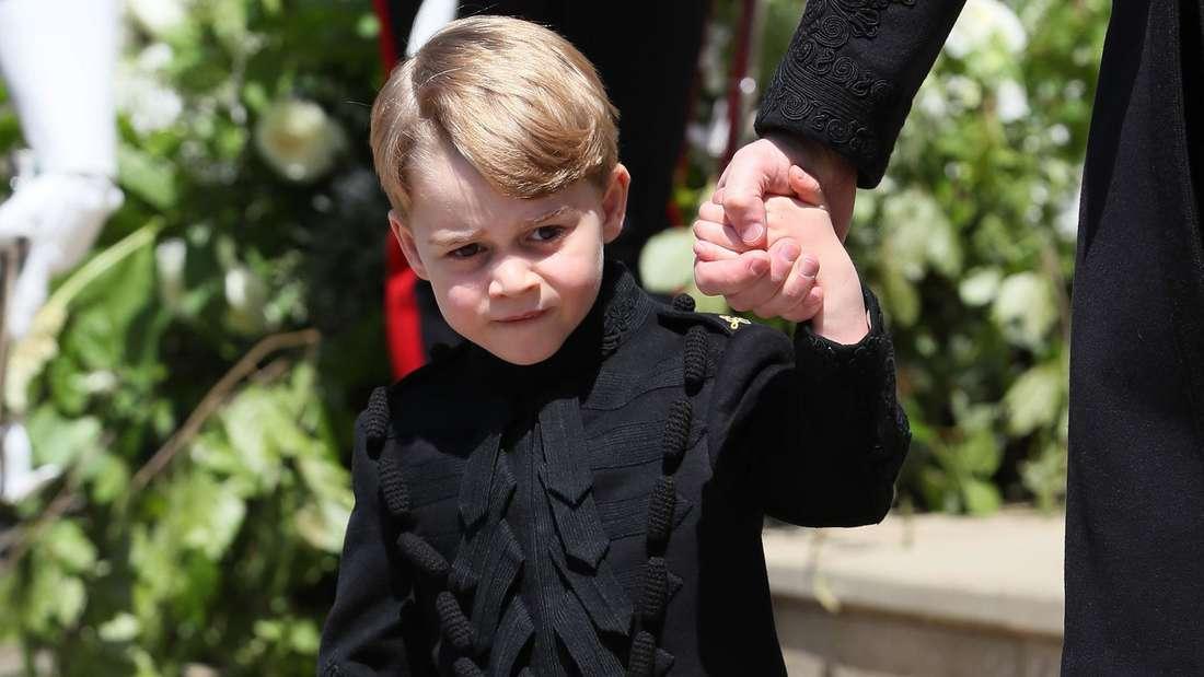 Prinz George hält eine erwachsene Person an der Hand und läuft eine Treppe hinunter.